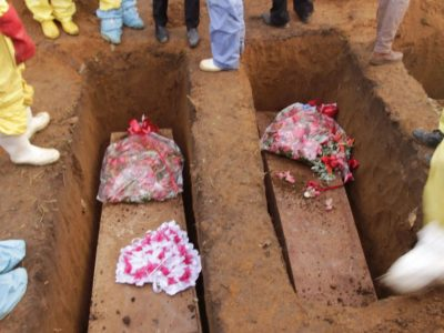 Volunteers  bury coffins during a mass funeral for victims of heavy flooding and mudslides in Regent at a cemetery in Sierra Leone, Freetown, Thursday, Aug. 17 , 2017. The government has begun burying the 350 people killed earlier this week in mudslides in Sierra Leone's capital, and it warned Thursday of new danger from a large crack that has opened on a mountainside where residents were told to evacuate. (AP Photo/Kabba Kargbo )
